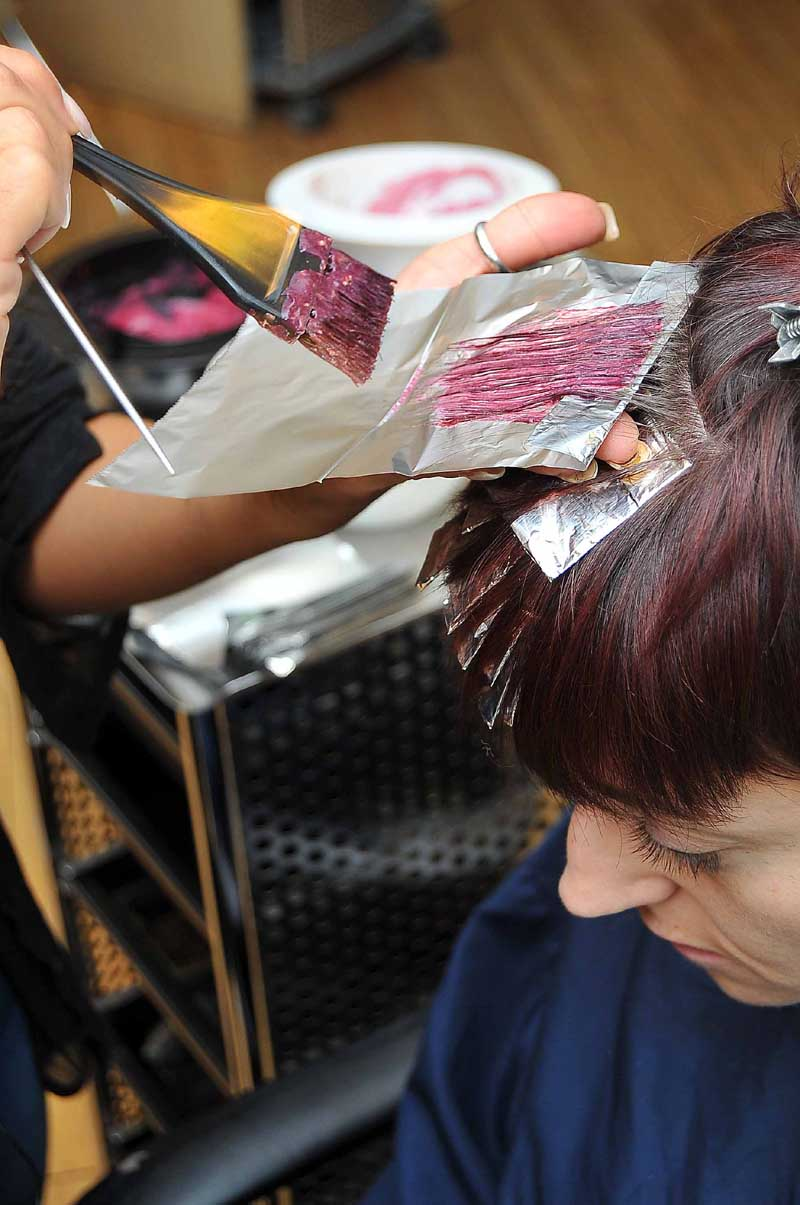 Lara uses a diagonal section to colour the hair. The part of the roots that she leaves out will have a different colour applied.